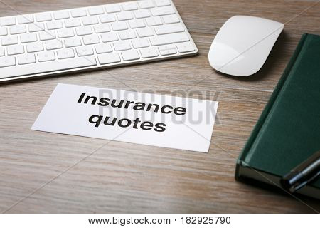 Card with text INSURANCE QUOTES on wooden table