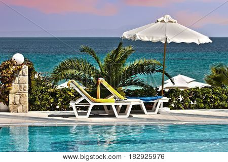 Plastic chair beside the pool with a perspective close to the sea. Relaxing Tanning beds beside swimming pool on remote beach