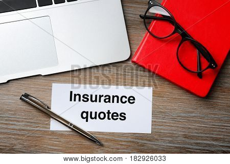 Card with text INSURANCE QUOTES and laptop on wooden background