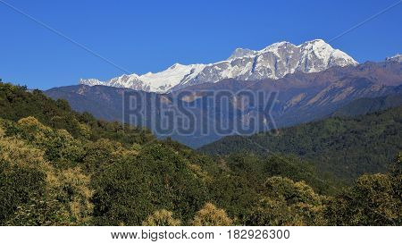 Green forests and snow capped Annapurna range. Landscape in the Himalayas Nepal.