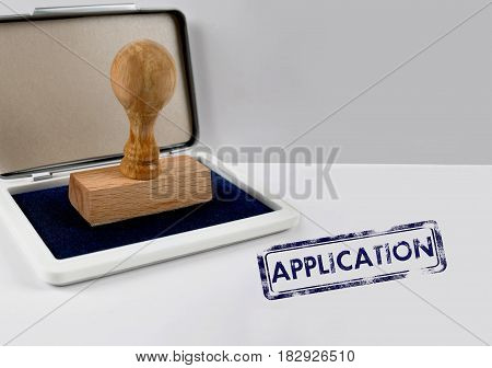 Wooden stamp on a desk white APPLICATION