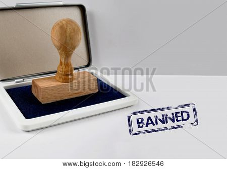 Wooden stamp on a white desk BANNED