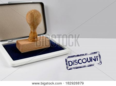 Wooden stamp on a white desk DISCOUNT