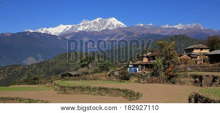 Fields and snow capped Annapurna range. Scene on the way to Ghale Gaun Nepal.