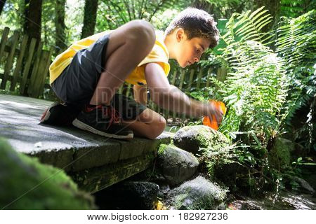 Soft focus image boy reaching into stream for drink cool clean fresh water from bush stream from baordwalk in natural environment.