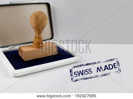 Wooden stamp with ink on desk SWISS MADE