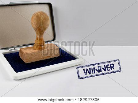 Wooden stamp on a white desk WINNER