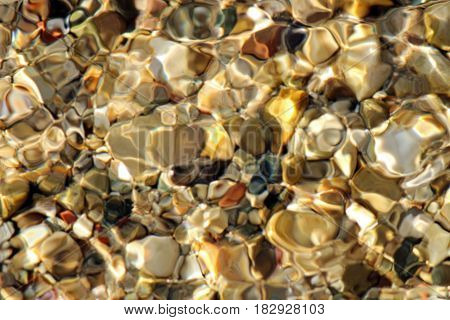 Beautiful pebbles under the cover of reflective water ripples.
