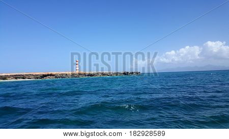 Sea view. White and red lighthouse from far away. Venezuelan ocean