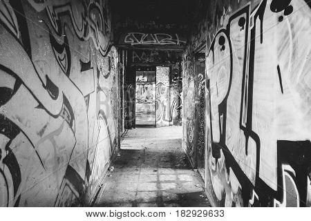 Messy small graffiti corridor in abandoned factory