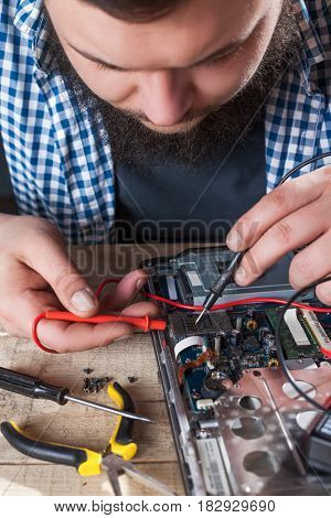 Engineer hands diagnostics laptop with multimeter