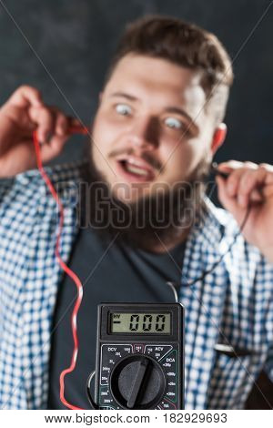 Male service engineer jokes with multimeter