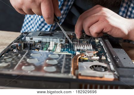 Engineer hands repairs laptop with screwdriver