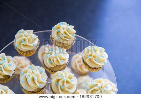 Vanilla bean mini cupcakes decorated with cyan and pink candy beads on a clear tiered tray up close.