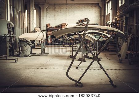 Classic car bodykit parts in painting workshop.