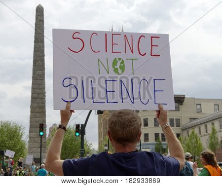 Asheville, North Carolina, USA: April 22, 2017 - A man holds up a sign on Eart Day that says