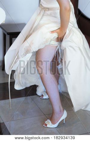 Sexual bride putting on wedding garter. Bride's hands and legs