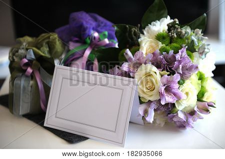 Wedding bouquet of flowers and wedding gift on blur background