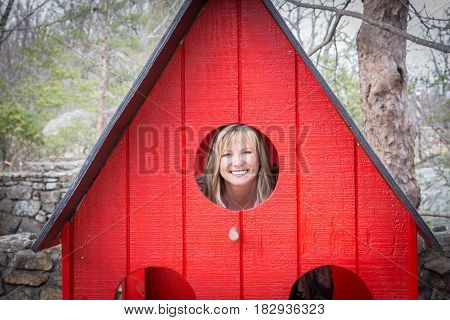 horizontal image of a grown caucasian woman playing around and being silly peeking through a round window from a child's red playhouse in the park.