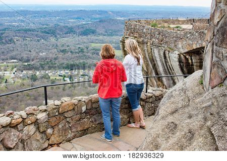 horizontal image of two caucasian women standing on a stone pathway high on a rock cliff looking down on a residential area in the spring time.