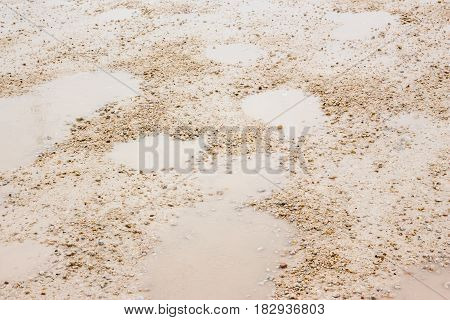horizontal close up image of a gravel road covered with pot holes full of rain water.