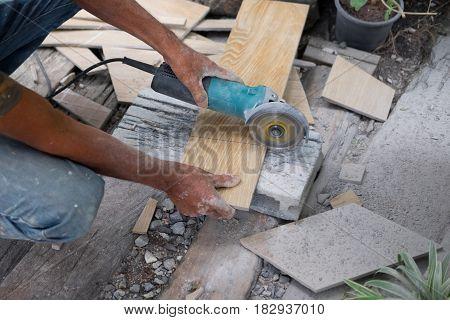 Worker using a hand circular saw to cut a tile for flooring and ceramic