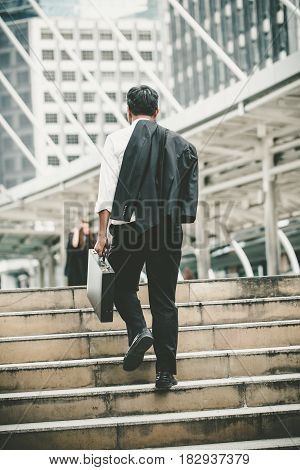 Disappointed Businessman Walking Up The Stairs In City. And Holding A Briefcase And Suit Jacket.