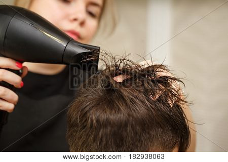 Professional hairdresser doing haircut men's hair. Drying hair with a hairdryer. Beauty saloon. Male beauty. The client is a hipster.