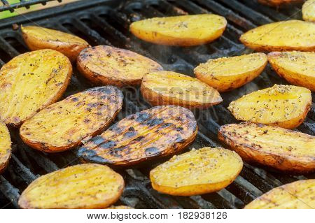 Potatoes and meat roasted on skewers BBQ grill Potatoes On Hot BBQ Charcoal Grill