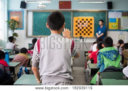 Chinese Schoolboy Pointing His Finger At The Bord