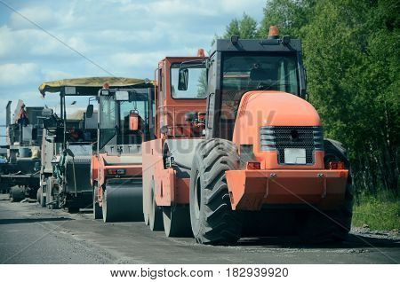 Tractor, roller , truck on the road repair site. Road construction equipment. Road repair concept.