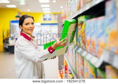 sales clerk refilling shelves at the supermarket