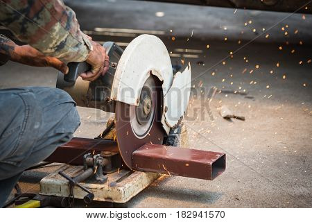 dark tone image of mechanic use cut off saw machine cutting steel unsafe on protection
