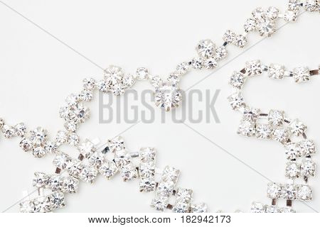 A beautiful diamond halo and white gold pendant dangles from a chain. Fine Jewelry necklace isolated on a white background with shadow and reflection poster