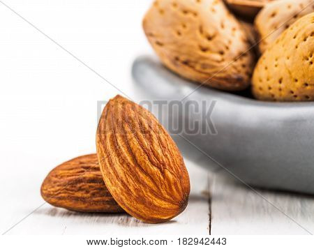 Extreme close up view on almond on white wooden background with copy space. Isolated one edge
