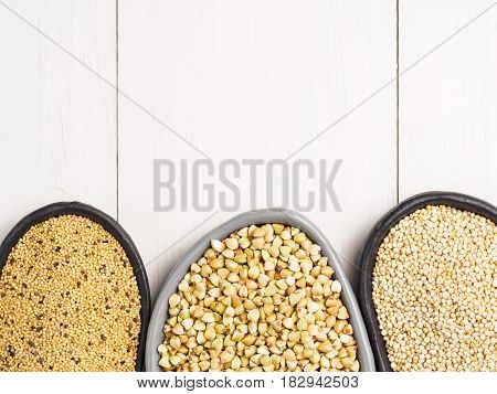 Green buckwheat, amaranth seeds and quinoa in trendy plates on white wooden table. Superfoods concept. Top view or flat lay. Copy space.