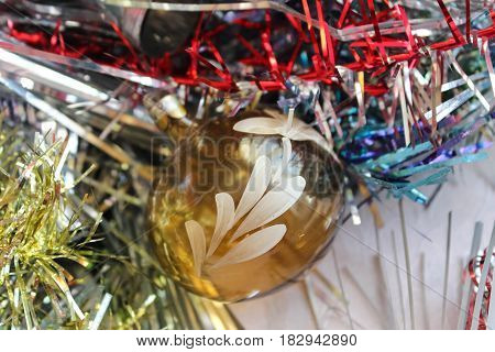 Yellow ball and multi-colored tinsel for a Christmas tree