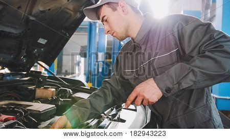 Mechanic in overalls checks level of engine oil in the car - automobile service repairing, close up