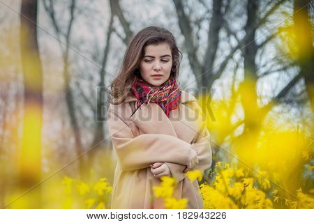 Beautiful teen girl, wearing trendy oversize beige coat and colorful scarf, standing in a spring park near blooming bushes with yellow flowers