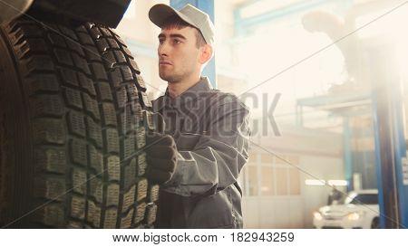 Car service - a mechanic checks the wheel of SUV, wide angle, horizontal