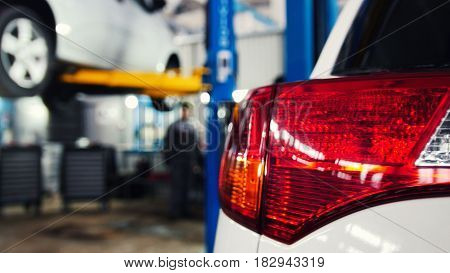 Automobile service - two mechanics standing near lifted automobile, slider