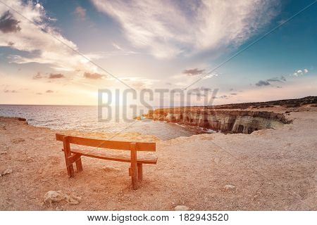 sunset in Cyprus - Mediterranean Sea coast. Sea Caves near Ayia Napa. the bench in the background of space. you can sit and think about life