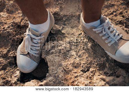 closeup of shoes on a background of stones on the coast. Cyprus - Mediterranean Sea coast. Sea Caves near Ayia Napa
