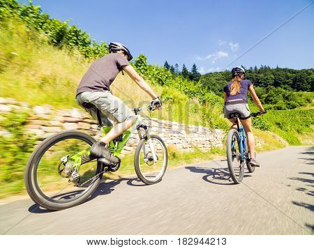 Young couple riding their mountain bikes in summer
