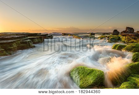 Wave flows over weathered rocks and boulders at Turimatta in sunrise. Sydney Australia