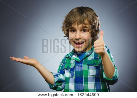 Happy child keeps something on hand and showing thumbs up. Closeup Portrait of handsome boy smiling isolated on grey background