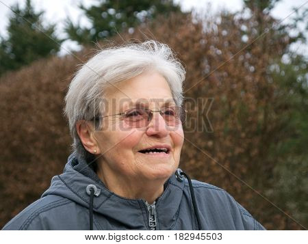 Happy old woman with glasses having fun