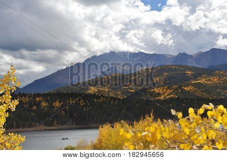 A view of Pikes Peak crested with snow and surrounded by storm clouds as seen from below behind Crystal Reservoir.
