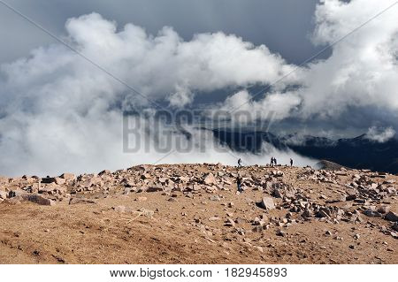 Clouds rise from beneath the edge of the mountain on Pikes Peak