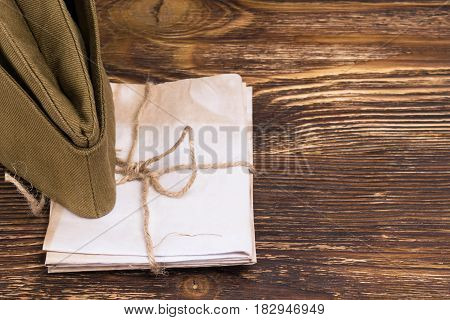 the pile of letters under the old military cap place the graphic on the right